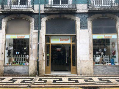 Edificio vestido con azulejos, balcones de hierro colado, empedrado portugués utilizado en la pavimentación de las aceras con adoquines en blanco y negro. Su escaparate con bonitas prendas y lanas de colores te invitan a entrar