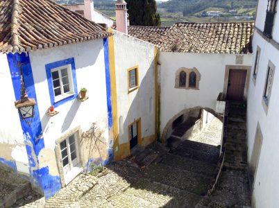 Calles adoquinadas, casas blancas con bordes en colores radiantes